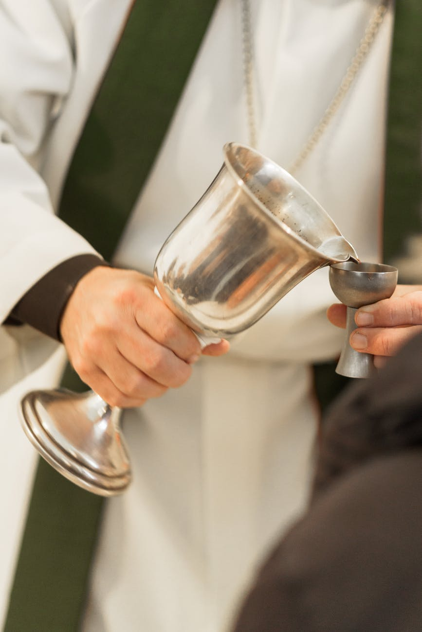 man in white suit holding clear wine glass